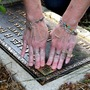 Lorie Miller affixes a QR code to her grandparents' gravestone. Miller and her husband are launching a business that will supply QR tags and maintain a website featuring the deceased.