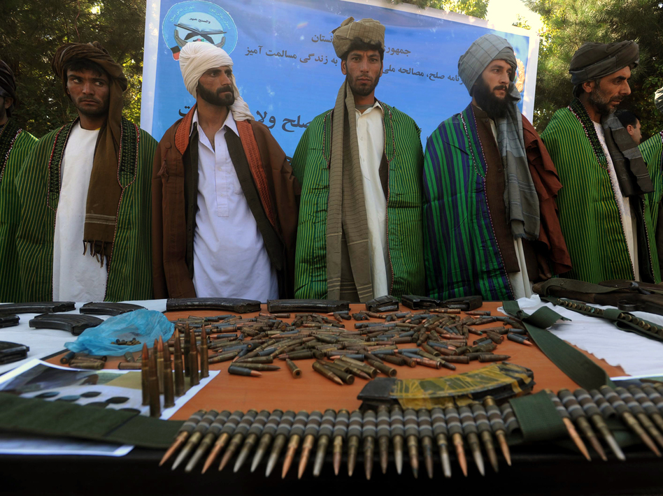 Former Taliban fighters display their weapons as they join Afghan government forces during a ceremony in Herat province on Sept. 18.