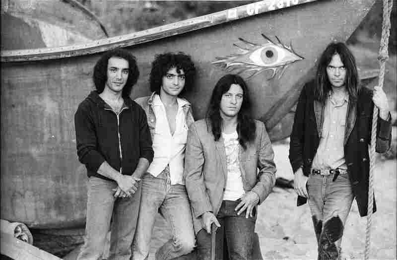"""With Crazy Horse, left to right: Ralph Molina, Billy Talbot, Frank """"Poncho"""" Sampedro, Neil Young. On Malibu Beach, 1975."""