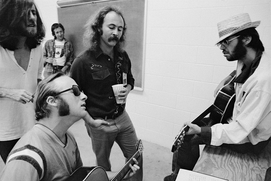 Left to right: Graham Nash, Stephen Stills, David Crosby and Neil Young, with Elliot Roberts in the background, backstage before a CSNY show in Denver, 1974. (© Joel Bernstein)
