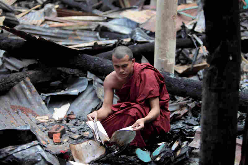 A Bangladeshi Buddhist monk checks the remains of burned religious books at a Buddhist temple which was torched in an overnight weekend attack in Ramu in the coastal district of Cox's Bazar, Bangladesh on Monday.