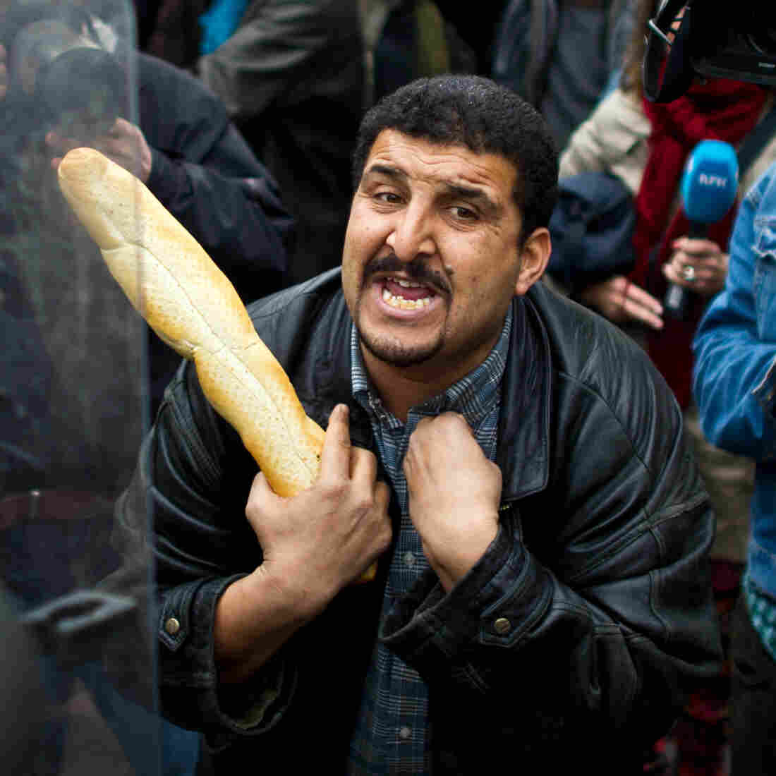 A Tunisian protester holds a baguette while taking to riot police in January 2011.