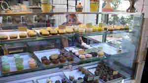 Nicole Kotovos arranges cupcakes in the case at her store in Athens.