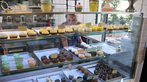 Nicole Kotovos arranges cupcakes in the case at her store in Athens. (NPR)
