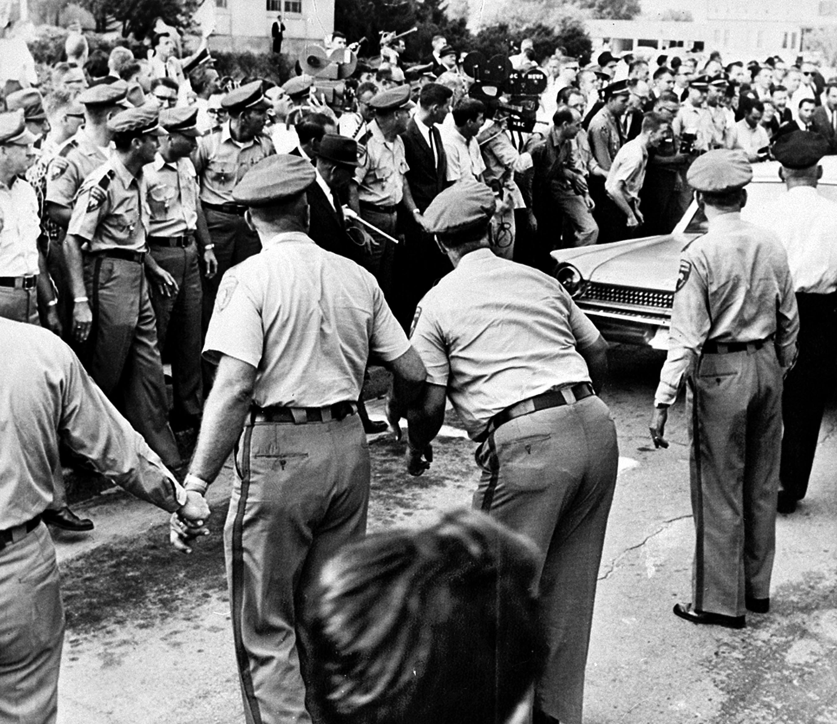 Policemen keep a cheering mob back as Meredith drives away after being refused admittance to the all-white university in Oxford, Miss. It took several attempts for him to enroll, as he was physically blocked on campus by Gov. Ross Barnett.