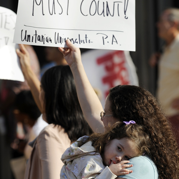 Emily Goldberg, with her daughter, Willa, 2, holds up a sign during the NAACP voter ID rally to protest against Pennsylvania's voter ID law on Sept. 13. Tuesday, a judge ordered that the law not be enforced in the Nov. 6 presidential election. (AP)