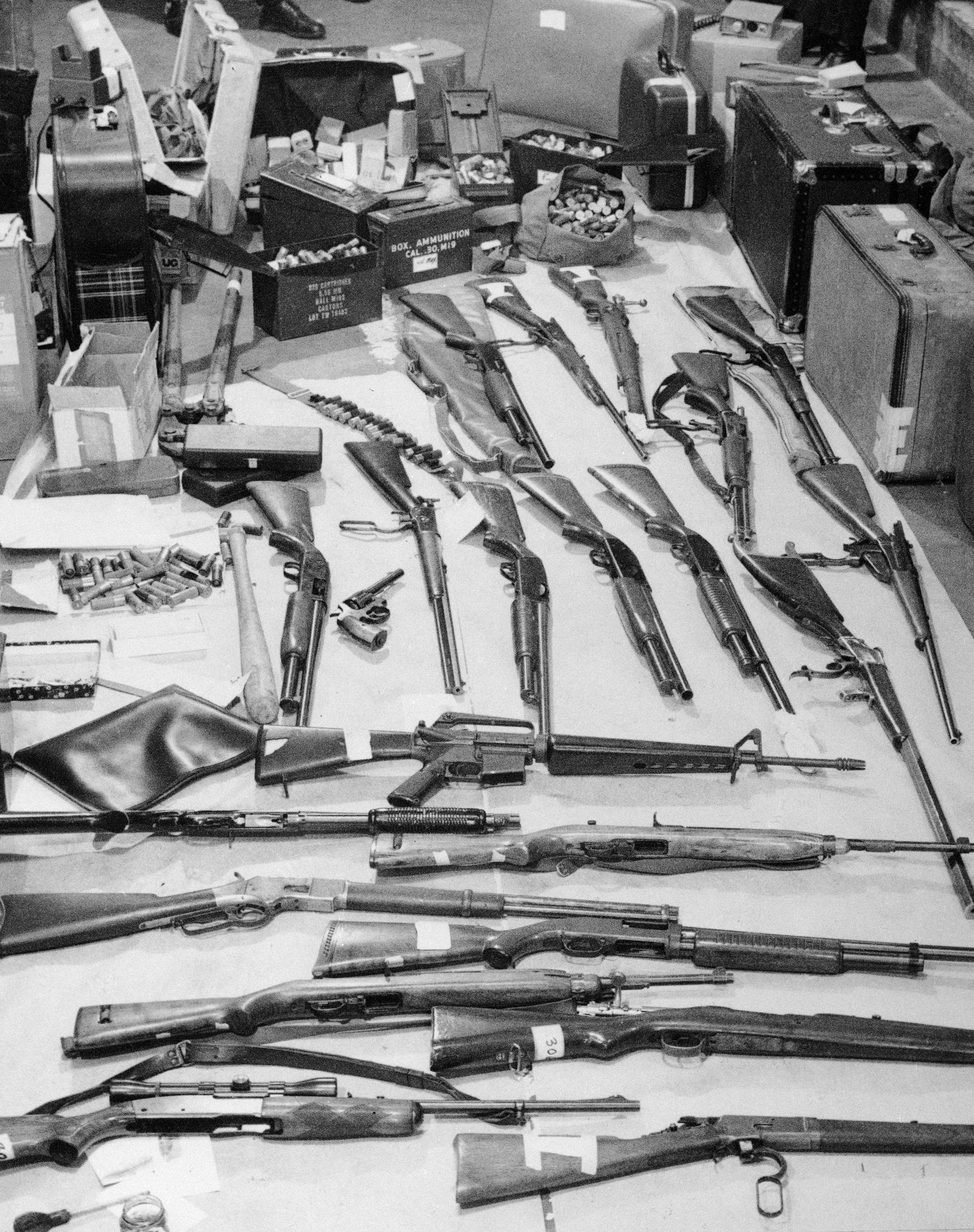 Police display guns and ammunition seized by officers on April 16, 1974, when 14 Black Panther Party members were arrested at the party�'s precinct headquarters. Bobby Seale called the raid �a plot to discredit them, timed to hurt the organization'�s chances of winning a majority of seats in next year'�s City Council.