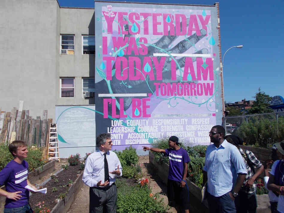 The Brownsville NeON probation office partnered with the public arts group Groundswell to establish a community garden in Brownsville. Local probationers designed and created the garden and mural. Here, the commissioner of the New York City Department of Probation, Vincent Schiraldi (second from left), meets with local advocates involved in the project.