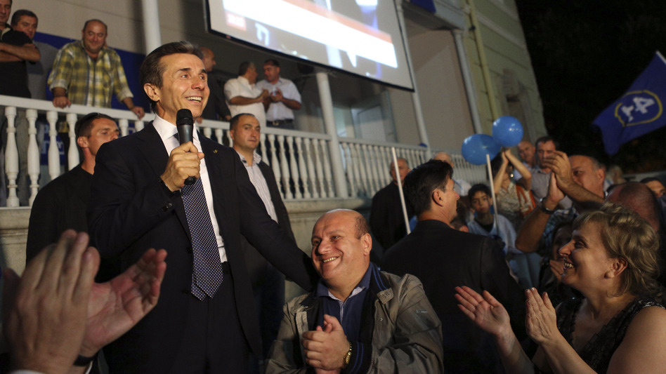 Georgian billionaire and opposition leader Bidzina Ivanishvili (left) reacts with supporters at his office on Monday. Ivanishvili defeated Georgian President Mikheil Saakashvili in the election, clearing the way for a new government. (AP)