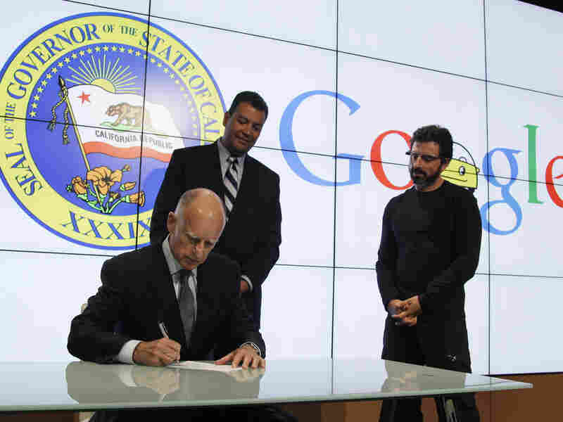 California Gov. Jerry Brown signs a bill for driverless cars as state Sen. Alex Padilla (left) and Google co-founder Sergey Brin look on. The legislation opens the way for driverless cars in the state.