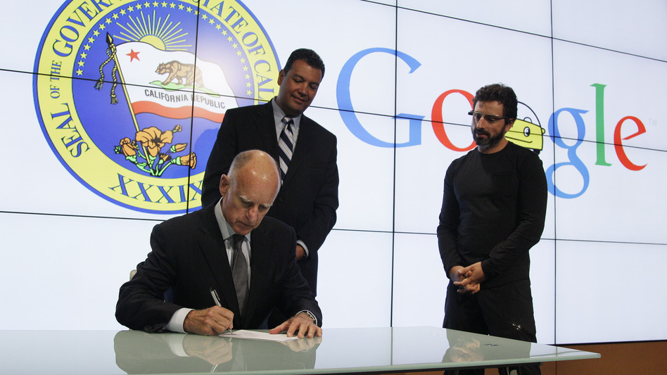 California Gov. Jerry Brown signs a bill for driverless cars as state Sen. Alex Padilla (left) and Google co-founder Sergey Brin look on. The legislation opens the way for driverless cars in the state. (AP)