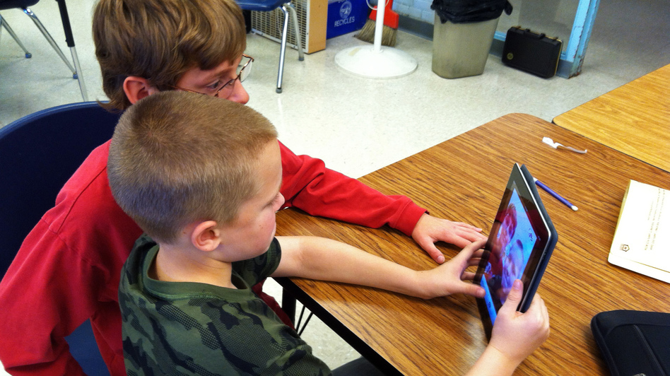 In Durham, N.H., Oyster River Middle School seventh-graders Patrick Beary and Morgan Bernier play with StoryKit, a free app that helps middle-schoolers put together simple presentations, and elementary students make storybooks. (New Hampshire Public Radio)