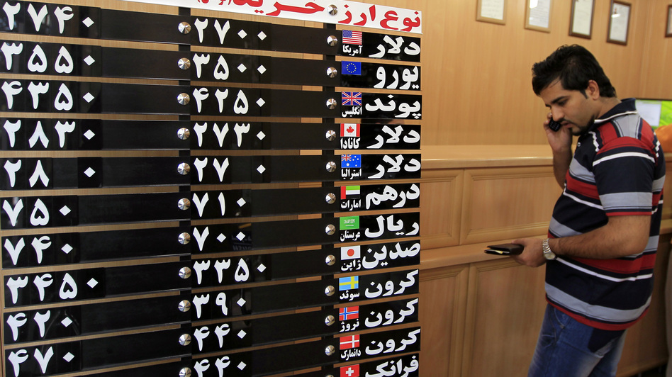 An Iranian man checks the rates of foreign currencies at a currency exchange bureau in central Tehran on Sept. 29. The Iranian currency lost nearly one-third of its value in a day over the weekend. (UPI/Landov)