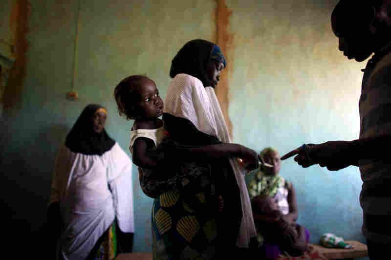 Women and their children wait for medication at the clinic in Dareta, Nigeria. Treating children with high levels of lead is a painstaking process that works only if their environment at home is free from lead.