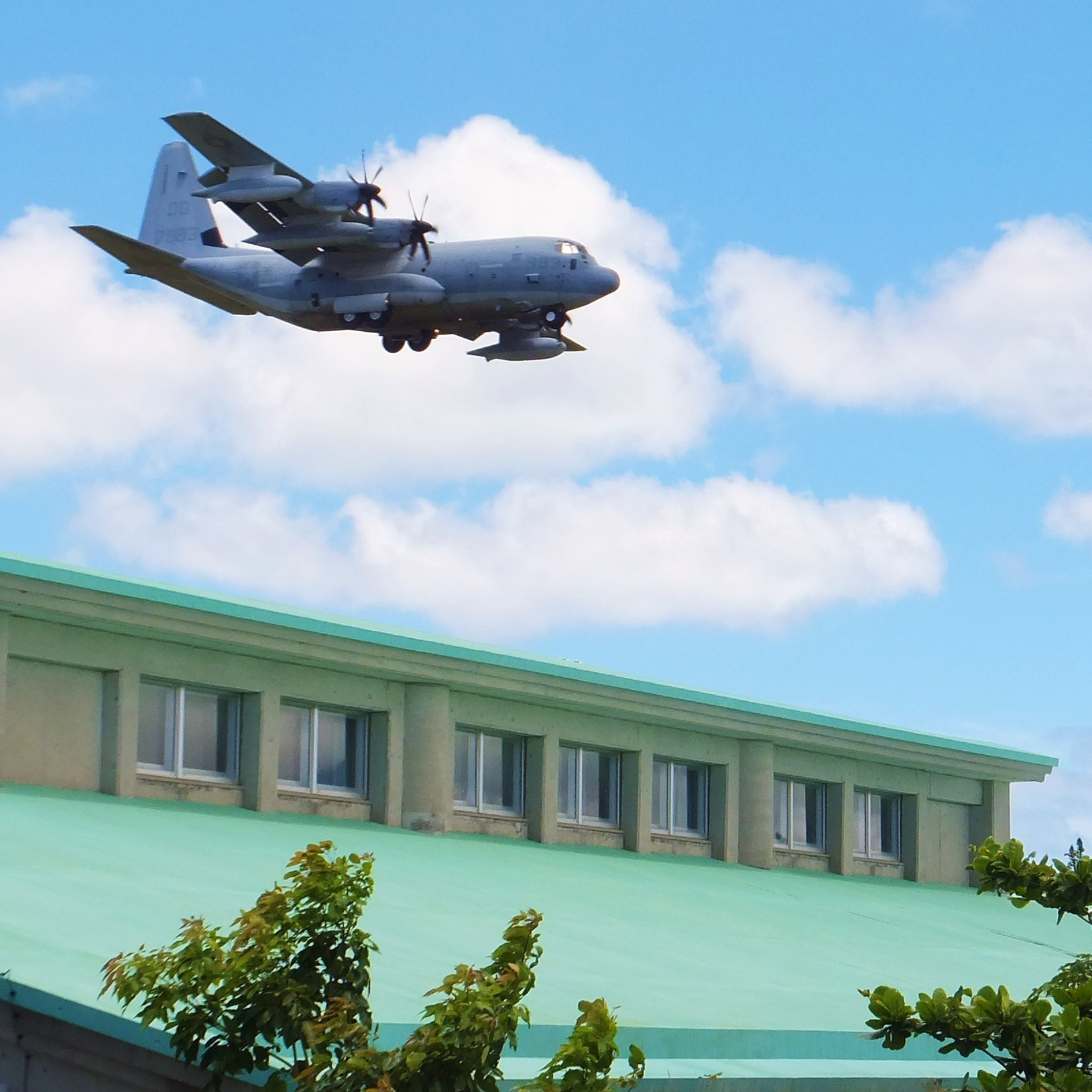 An Osprey flies over the Futenma No. 2 Elementary School in Ginowan city on Japan's southern island of Okinawa. Six Ospreys were deployed in Okinawa, drawing sharp reactions from residents amid persistent concerns about the aircraft's safety.