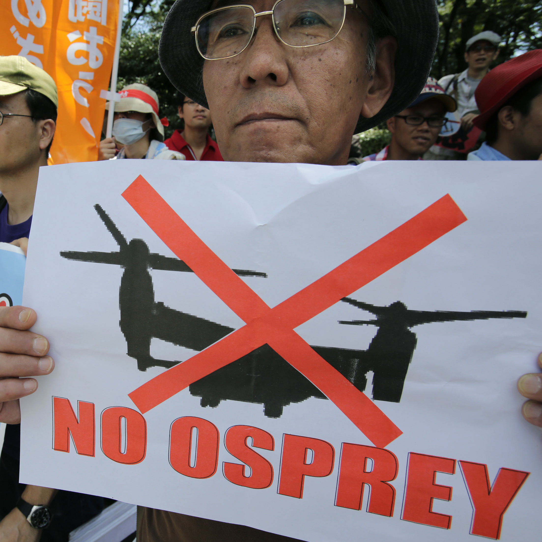 Demonstrators hold placards during a Sept. 9 rally outside the National Diet in Tokyo against the plan to deploy U.S. Osprey aircraft on Okinawa.