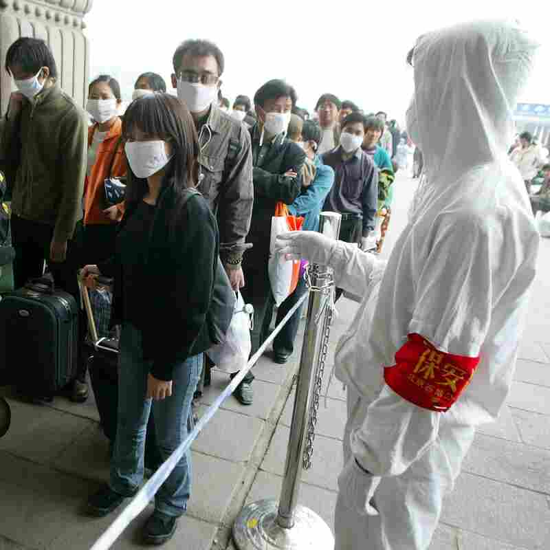 A railway worker wearing protective clothing to ward off the SARS virus controls a line of travelers as they wait to enter Beijing's West Railway Station Tuesday in 2003.