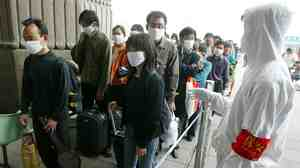 A railway worker wearing protective clothing to ward off the SARS virus controls a line of travelers as they wait to enter Beijing's West