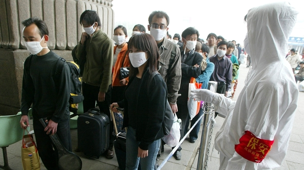 A railway worker wearing protective clothing to ward off the SARS virus controls a line of travelers as they wait to enter Beijing's West Railway Station Tuesday in 2003. (AP)