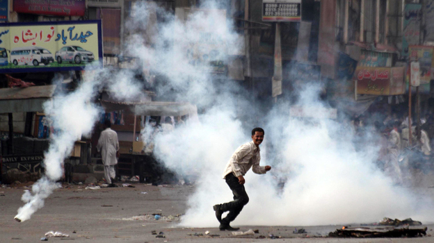 A demonstrator reacts after Pakistani policemen fire tear gas during a protest against power cuts in Karachi in June. Pakistan suffers from a massive energy crisis, one of several factors contributing to the country's severe economic troubles. (AFP/Getty Images)