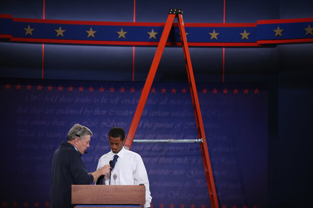 University student Dia Mohamed gets a wireless microphone put on his tie as he stands in for President Barack Obama during rehearsal for the first presidential debate in the Ritchie Center at the University of Denver on Tuesday.