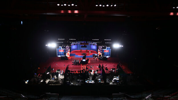 Workers prepare Wednesday for the presidential debate at the University of Denver. Experts differ over whether even a televised debate is a good forum for sharing very specific details about policy proposals.