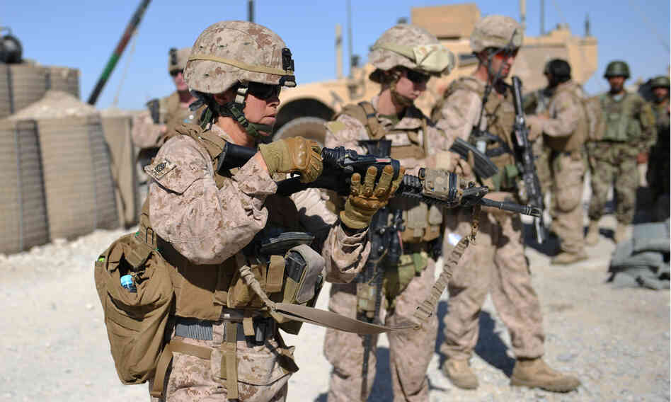 Female Marines unload their rifles after a patrol with Afghan soldiers in Helmand prov