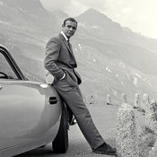 Sean Connery relaxes on the bumper of his Aston Martin DB5 during the filming of location scenes for Goldfinger in the Swiss Alps in 1964.