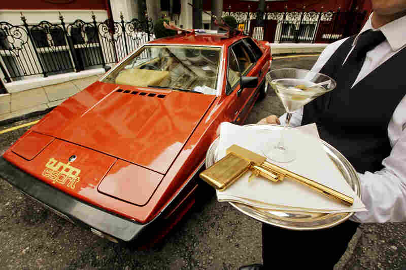 A model holds a limited-edition gold-plated Golden Gun replica, near a Lotus Turbo Esprit car from 1981's For Your Eyes Only.