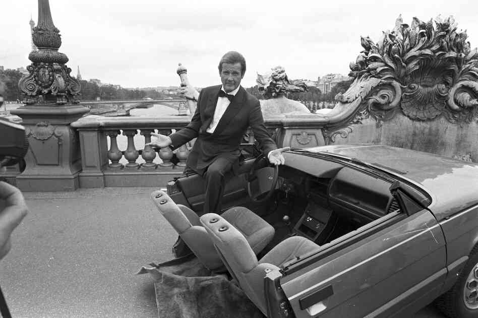 Roger Moore with half a car during the filming of A View to a Kill in Paris, 1984. Moore was part of the iconic series for more than a decade, playing Bond in seven consecutive films.