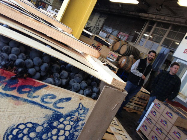 Customers at a Hartford produce market, choosing grapes to turn into homemade wine. (NPR)