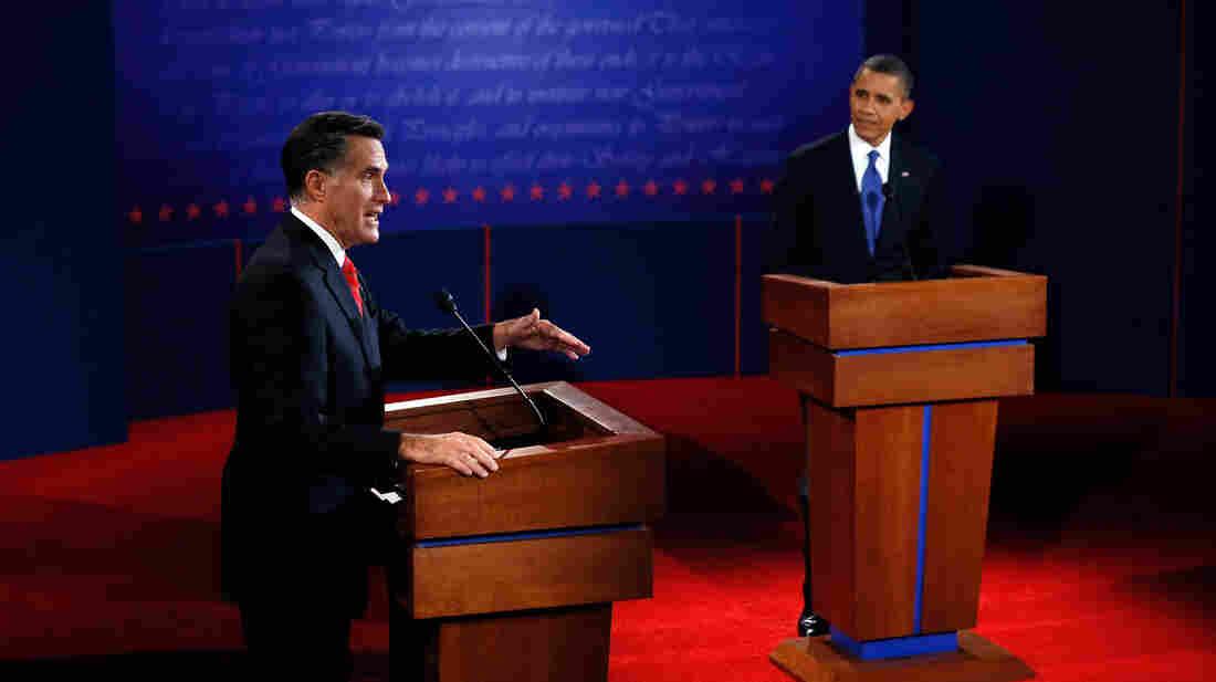 Mitt Romney makes his point as President Obama listens during Wednesday's debate in Denver.
