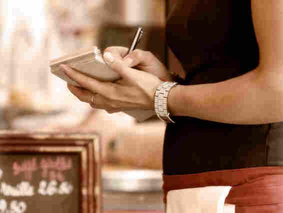 Waitress writes down an order.