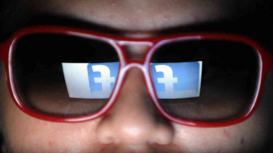Does he need to watch what he likes? Facebook's logo is reflected in the glasses of a student in Manila.