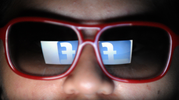 Does he need to watch what he likes? Facebook's logo is reflected in the glasses of a student in Manila. (AFP/Getty Images)