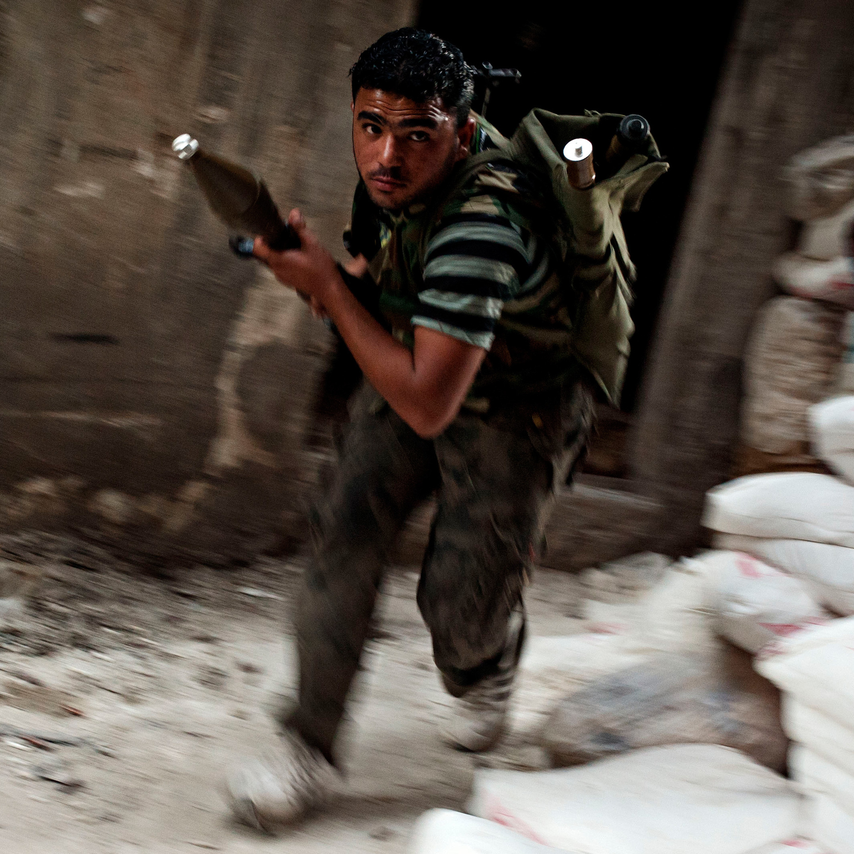 A Free Syrian Army fighter dodges sniper fire in the Salah Al Din neighborhood of Aleppo, Syria, on Aug. 22.