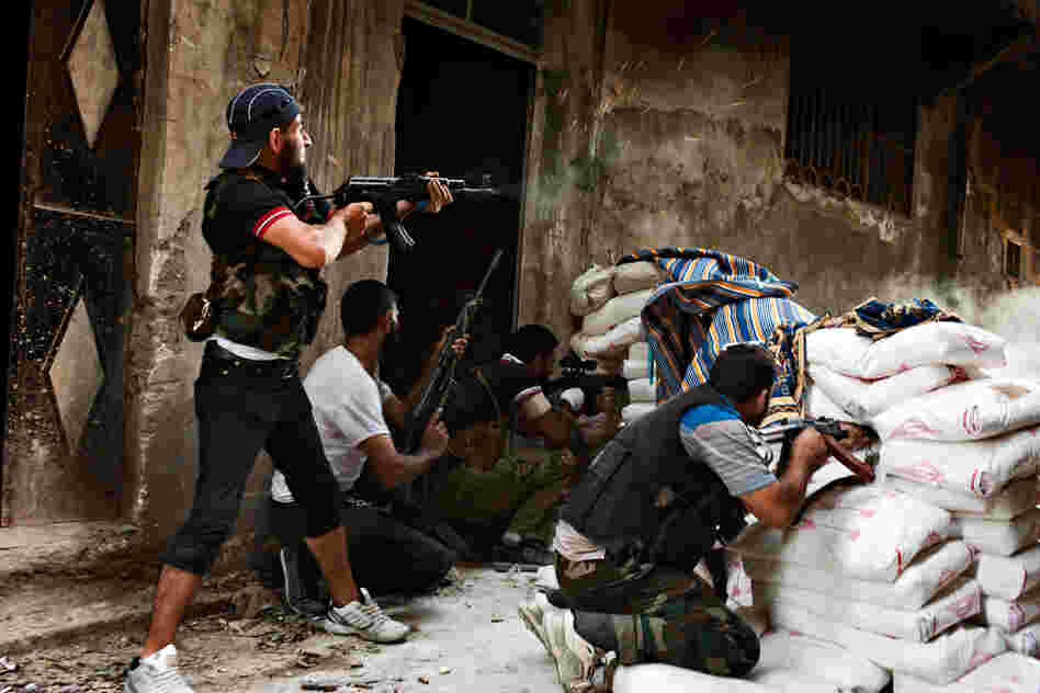Free Syrian Army fighters exchange fire with regime forces in the Salah Al Din neighborhood of Aleppo, Aug. 22.