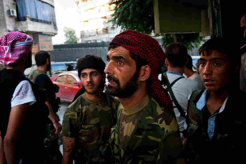 Free Syrian Army fighters take cover from a Syrian attack helicopter in the Sakhour neighborhood of Aleppo, Aug. 23.