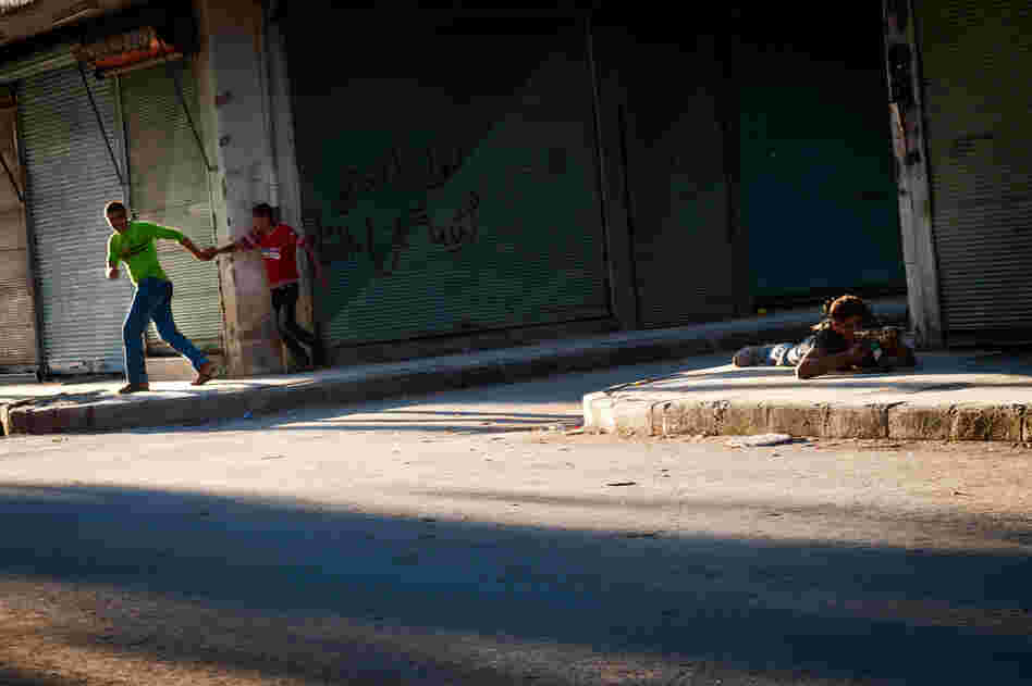 Young Syrians run for cover as a Free Syrian Army fighter returns sniper fire in the Bustan Pasha neighborhood of Aleppo, Aug. 21.