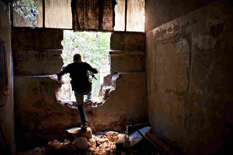 A Free Syrian Army fighter climbs through a damaged wall during fighting in the Saif Dawla neighborhood of Aleppo, Aug. 24.