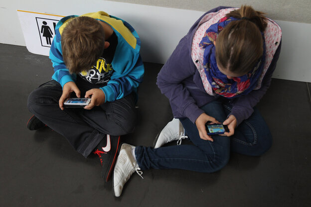 Children play video games on smartphones while attending a public event on September 22, 2012 in Ruesselsheim, Germany.