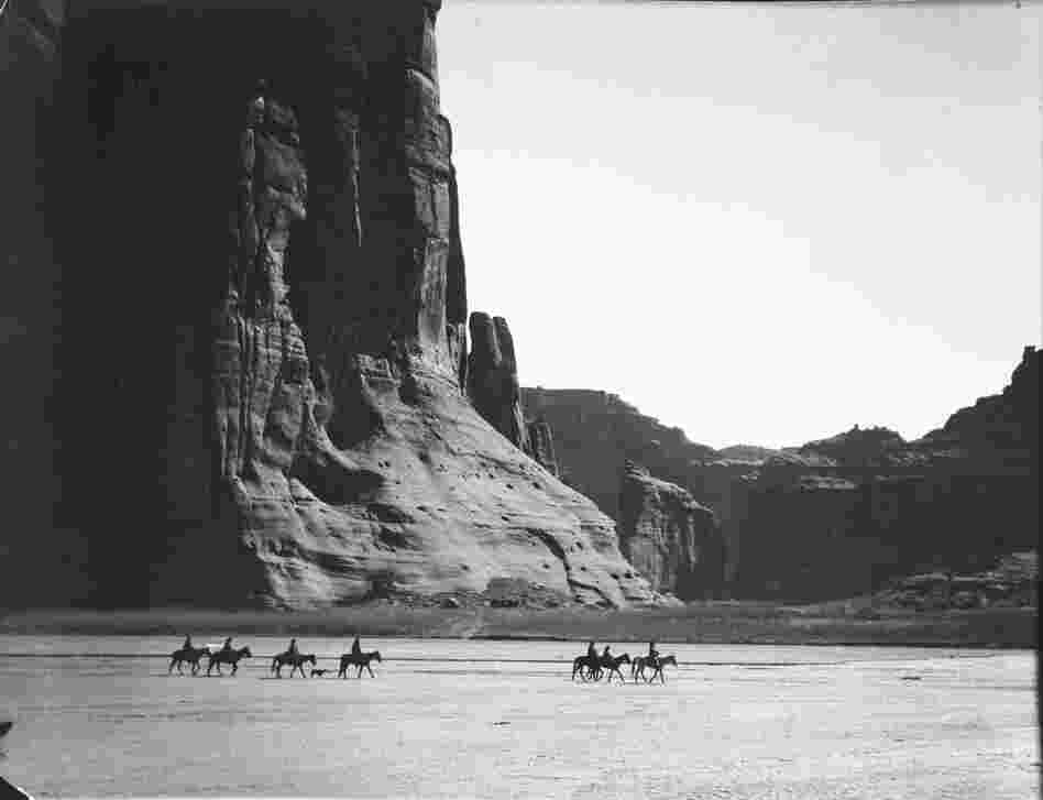 Cañon de Chelly, 1904. In the heart of the Navajo Nation, where stone and sky dwarf humans on horseback, the canyon is one of the most stunning places on Earth.