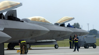 Air Force F-22 Raptors, made by Lockheed Martin, are prepared for flight operations at Langley Air Force Base. Despite the looming defense spending cuts that would go into effect in January if Congress does not pass a deficit reduction plan, Lockheed Martin and other defense contractors announced this week they would not issue layoff notices.