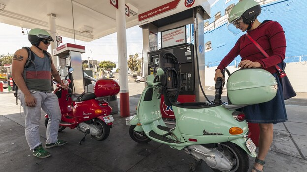Motorcyclists Hanna Gilan, right, and her son Chaim Gilan fill up their Vespa scooters with less than two gallons at a gas station in the Echo Park district of Los Angeles on Oct. 4, 2012. (AP)