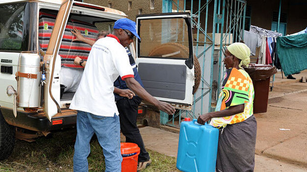 After testing negative for Ebola, Magdalena Nyamurungi returns home with a new set of belongings from the World Health Organization. Medical workers burned and buried her possessions when they suspected she was infected. (Courtesy of WHO)