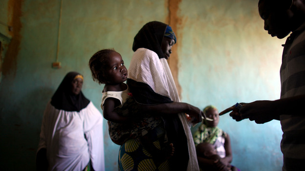 Women and their children wait for medication and instructions on how to use it at the clinic in Dareta, Nigeria. Treating children with high levels of lead is a painstaking process that works only if their environment at home is free from lead. (NPR)