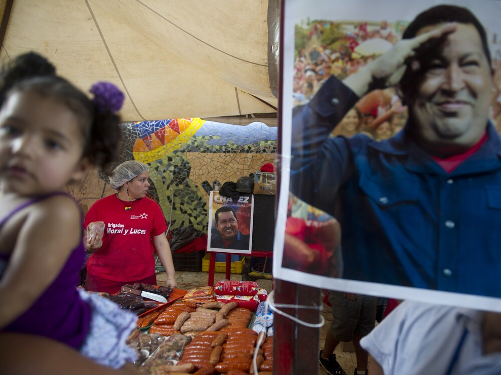 A picture of Venezuelan President Hugo Chavez hangs at a state-run market that provides subsidized food and basic goods in Caracas on Oct. 3.