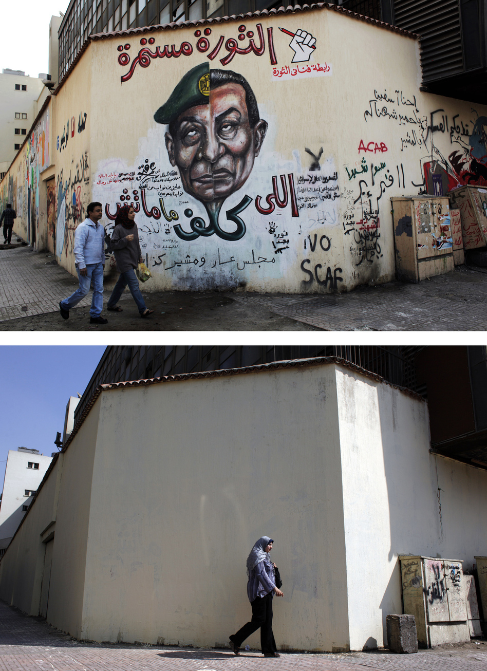 A mural (pictured above in March) was whitewashed (below) during a cleanup campaign in Cairo's Tahrir Square in September. Graffiti artists repainted the wall soon after. (AP)