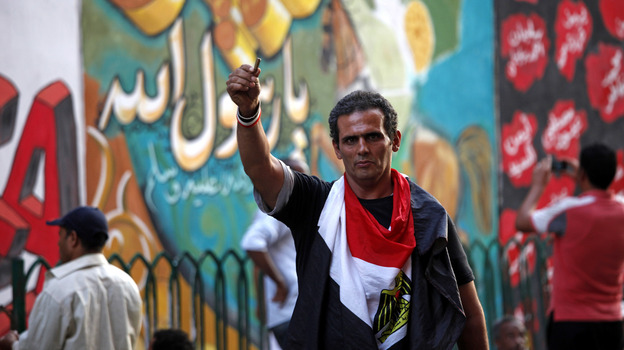 An Egyptian man waves a bullet casing in front of a mural that was painted on a recently whitewashed wall in Tahrir Square in Cairo. (AP)