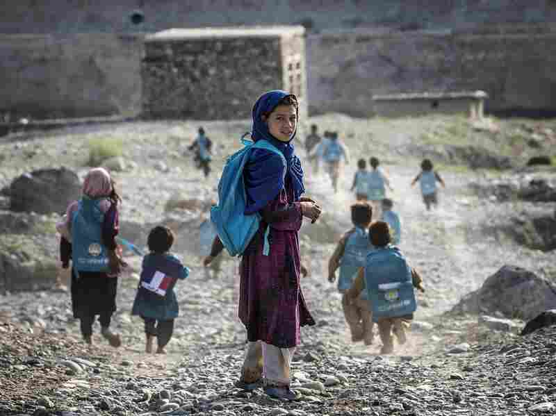 Afghan children run to school on Sept. 24. Whoever takes over as the next U.S. president will have to determine how many troops will remain after the December 2014 deadline to help with long-term security.